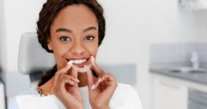 Woman smiling, holding a clear aligner